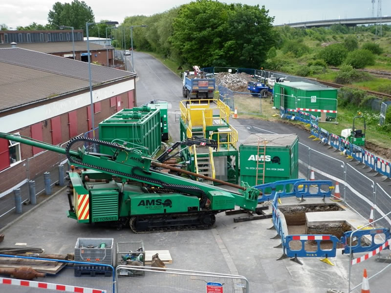 The AMS No-Dig Powerbore 70 tonne drill rig set up on site. The mud recycling system can also be seen behind the drilling rig